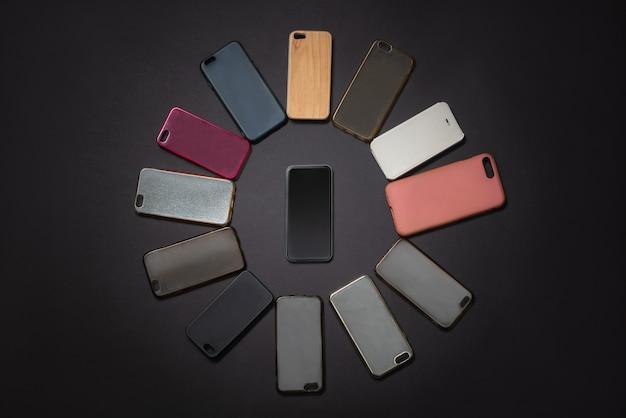 Stapel mehrfarbiger kunststoff-rückabdeckungen für mobiltelefone auf schwarz mit einem telefon an der seite