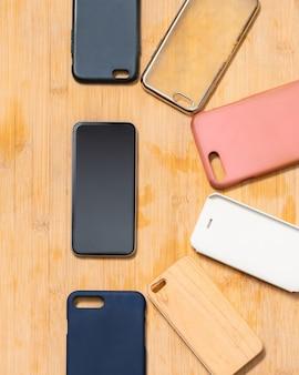 Stapel mehrfarbiger plastikrückabdeckungen für handys auf holz mit einem telefon an der seite