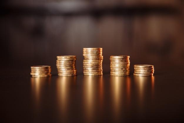 Stapel münzen auf einem holztisch.