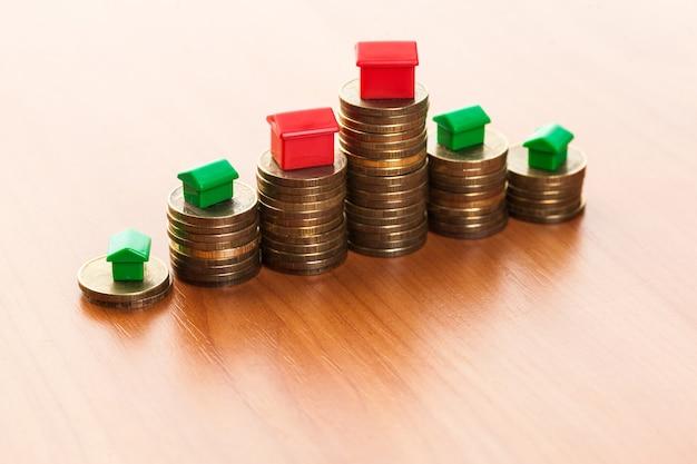 Stapel münzen, grünes und rotes haus. hypothekenkonzept durch geldhaus von den münzen
