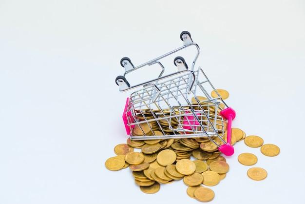 Stapel münzen und einkaufswagen oder supermarktlaufkatze