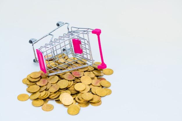 Stapel münzen und warenkorb- oder supermarktlaufkatze auf weißem hintergrund