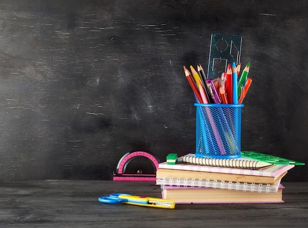 Stapel notizbücher, blaues glas mit mehrfarbigen hölzernen bleistiften und stift