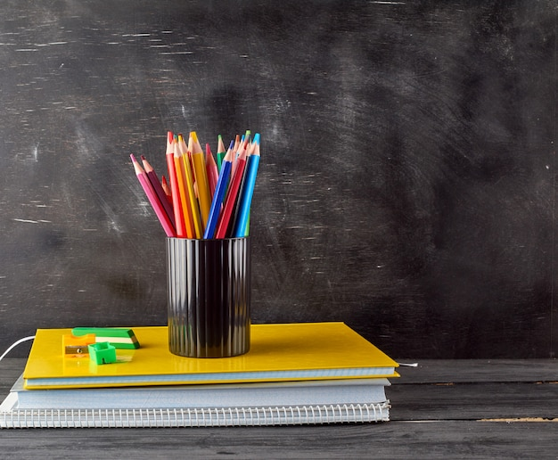 Stapel notizbücher, schwarzes briefpapierglas mit mehrfarbigen hölzernen bleistiften