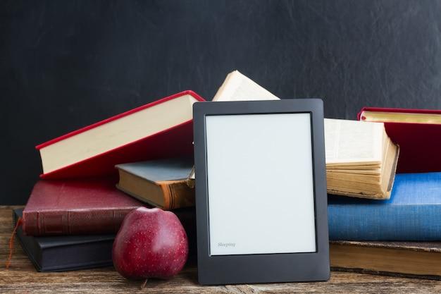 Stapel papierbücher mit modernem e-book