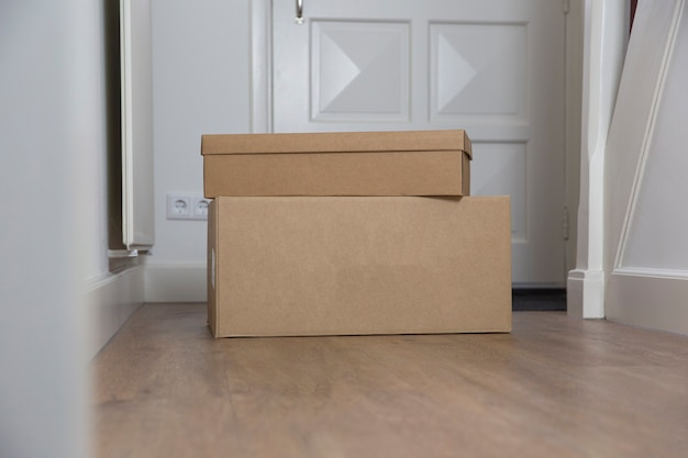 Stapel pappkartons leer im flur des neuen hauses auf dem boden umzugslager oder lieferung