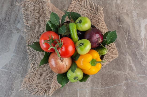 Stapel paprika, zwiebel, rote tomaten, grüne tomaten, gurke, rote zwiebel und blätter auf einem stück stoff, auf marmor.