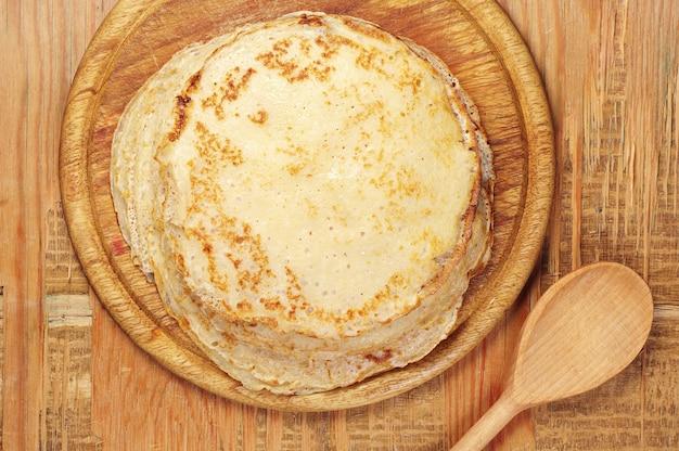 Stapel pfannkuchen auf alter hölzerner tischoberansicht