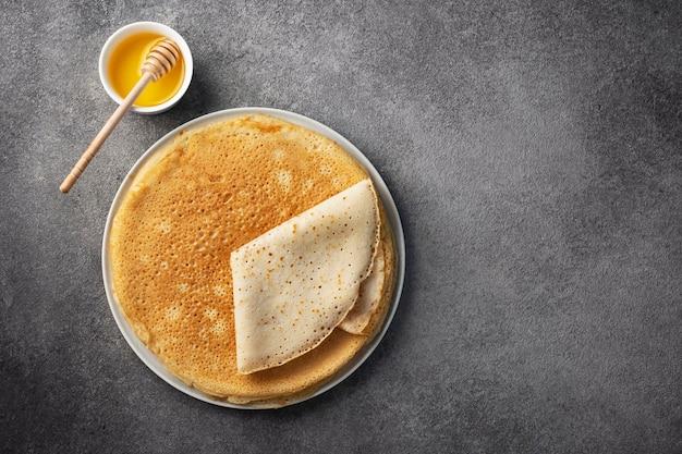 Stapel pfannkuchen auf einem teller mit honig, maslenitsa