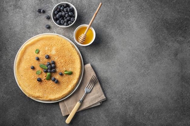 Stapel pfannkuchen auf einem teller mit honig und beeren, maslenitsa