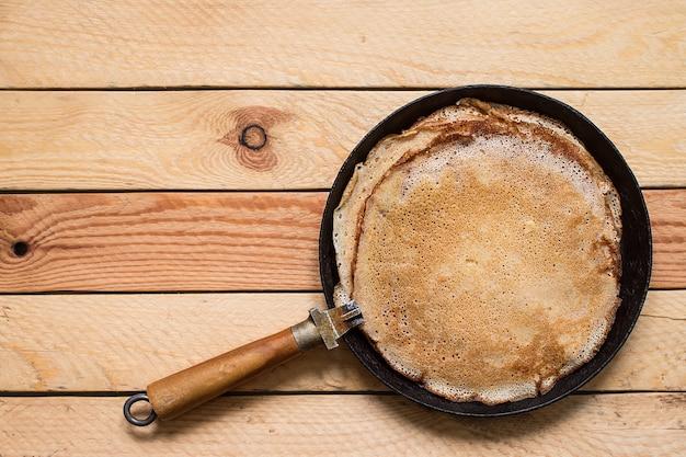 Stapel pfannkuchen auf einer gusseisernen pfanne.