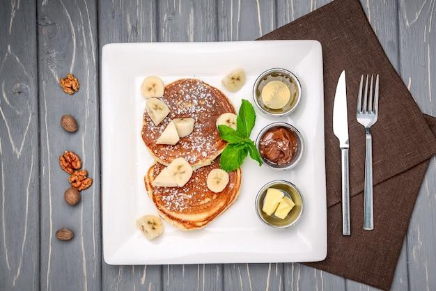Stapel pfannkuchen der türkischen art mit einer banane und einer schokolade