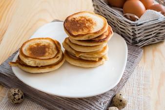 Stapel Pfannkuchen in der weißen Untertasse auf hellem Holztisch