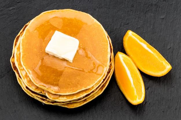 Stapel pfannkuchen in sirup mit orangen auf dunklem hintergrund