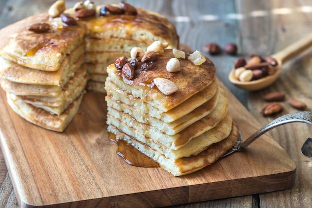 Stapel pfannkuchen mit ahornsirup und nüssen
