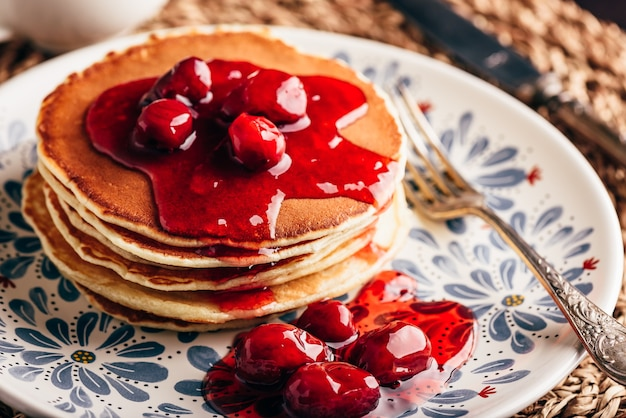 Stapel pfannkuchen mit hartriegel-beeren-marmelade auf weißem teller mit reich verziert Premium Fotos