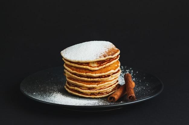 Stapel pfannkuchen mit zuckerpulver und zimt auf dunklem hintergrund mit kopierraum