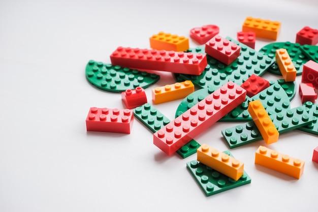 Stapel plastikspielzeugblöcke. mehrfarbige plastikbausteine des designers. konstrukteure für kinder, würfel. spiele für die motorische entwicklung von gedächtnis und verstand.