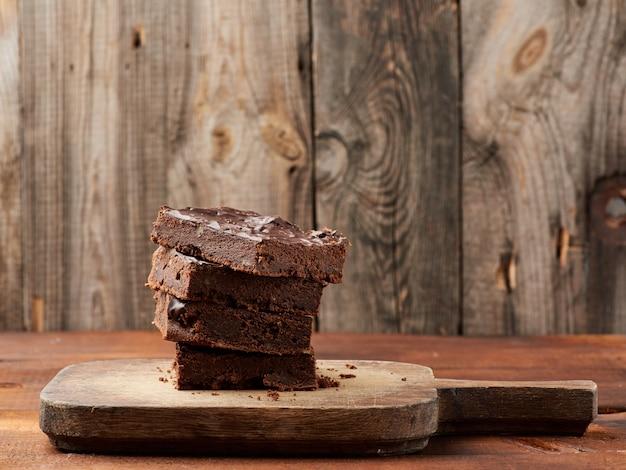 Stapel quadrat gebackene scheiben des schokoladenkuchenschokoladenkuchens mit walnüssen