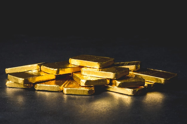 Stapel reine goldbarren auf schwarzem hintergrund