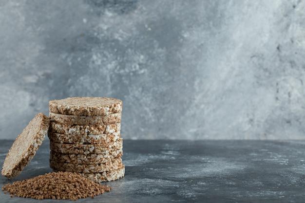 Stapel reiskuchen und haufen buchweizen auf marmoroberfläche