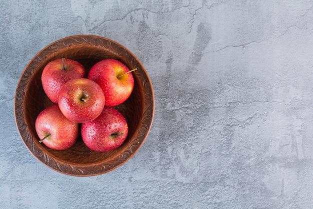 Stapel roter äpfel in der schüssel über grau.