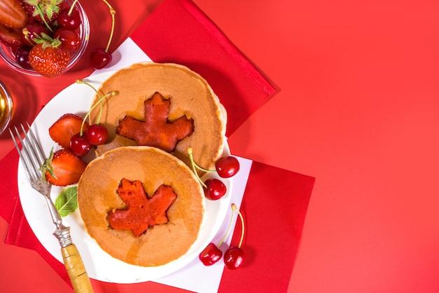 Stapel roter und weißer pfannkuchen mit kreativer dekoration aus ahornblättern