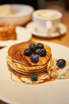 Stapel runde pfannkuchen mit blaubeereis und karamellsirup nahaufnahme im kaffeehaus