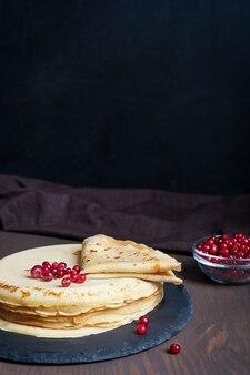 Stapel russischer traditioneller blinis oder dünner pfannkuchen mit roten beeren auf dunkelbraunem holztisch