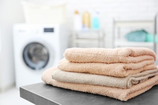 Stapel saubere handtücher auf dem tisch im waschsalon
