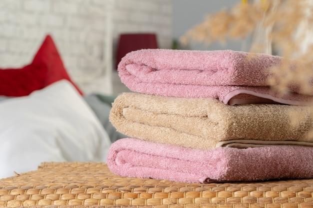 Stapel saubere tücher auf holztisch im schlafzimmer