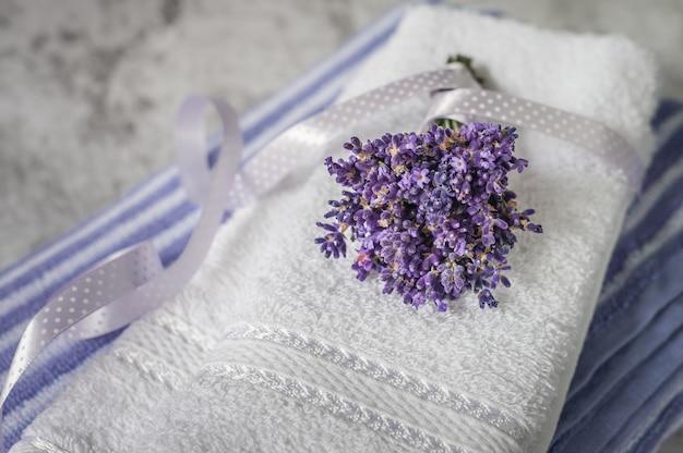 Stapel saubere weiche tücher mit einem bündel lavendel auf hellgrauem.