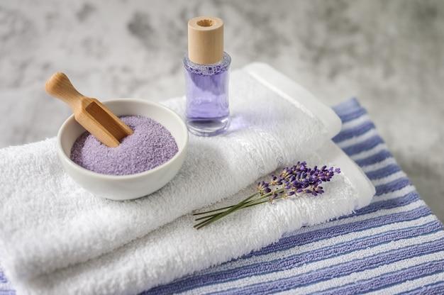 Stapel saubere weiche tücher mit einem bündel lavendel, badesalz und lufterfrischer auf hellgrauem. badekurorttücher gegen eine strukturierte wand. minimalismus, weicher fokus. spa.