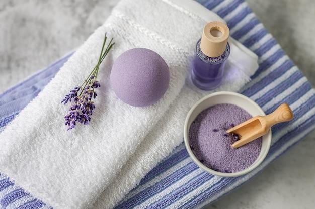 Stapel saubere weiche tücher mit einem bündel lavendel, badesalz und lufterfrischer auf hellgrauem.