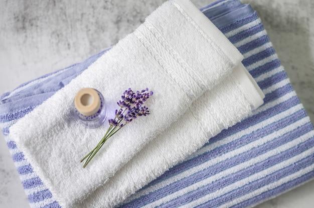 Stapel saubere weiche tücher mit einem bündel lavendel und lufterfrischer auf hellgrauem. badekurorttücher gegen eine strukturierte wand. minimalismus, weichzeichnung, draufsicht.