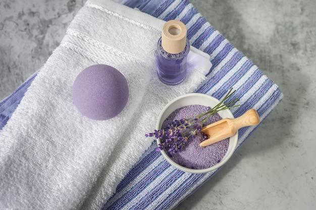 Stapel saubere weiche tücher mit lavendel, lufterfrischer und badesalz auf hellgrauem. badekurorttücher gegen eine strukturierte wand. minimalismus, weichzeichnung, draufsicht.