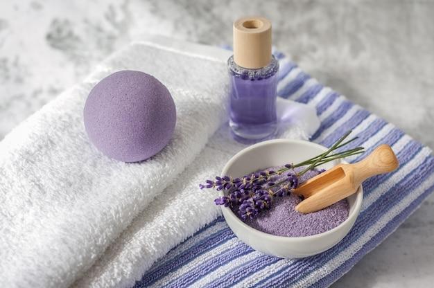 Stapel saubere weiche tücher mit lavendel, lufterfrischer und badesalz auf hellgrauem.