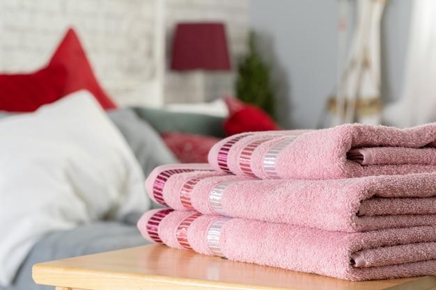 Stapel sauberer handtücher auf holztisch im schlafzimmer