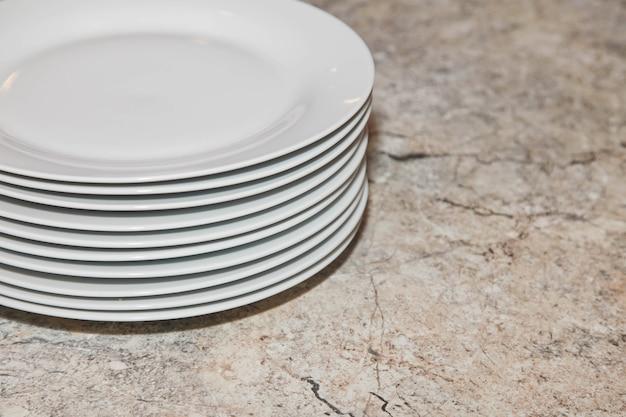 Stapel sauberer teller auf der texturtabelle. hintergrund von sauberem geschirr in der küche. platz kopieren