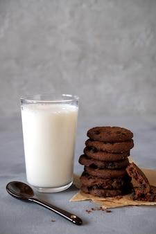 Stapel schokoladenkeks und glas milch. auf grauem hintergrund