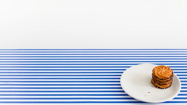 Stapel schokoladenplätzchen auf weißer platte über dem streifenhintergrund