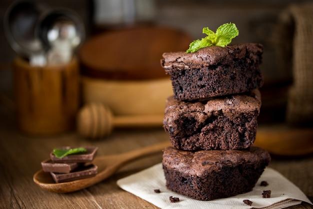 Stapel schokoladenschokoladenkuchen auf hölzernem hintergrund mit tadellosem blatt auf die oberseite, selbst gemachte bäckerei