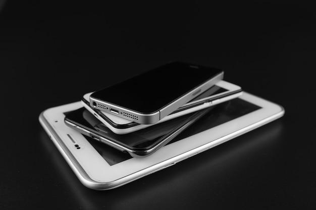 Stapel spitzen-smartphones auf schwarzem schreibtisch.