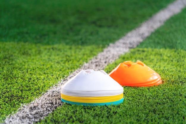 Stapel sportmarkierungskegel auf trainingsplatz mit weißer grenzlinie.