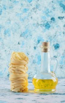 Stapel tagliatelle-nester und glas olivenöl auf blau.