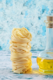 Stapel tagliatelle-nester und glas olivenöl auf blauem hintergrund. foto in hoher qualität