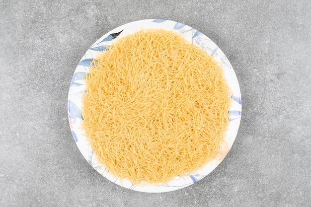 Stapel ungekochter makkaroni auf weißem teller