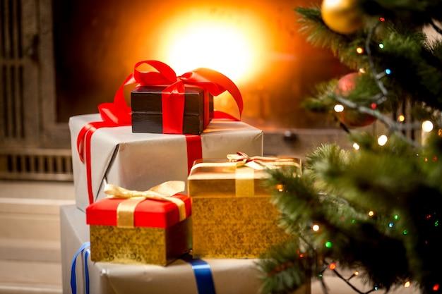 Stapel verpackter geschenkboxen unter dem weihnachtsbaum am kamin