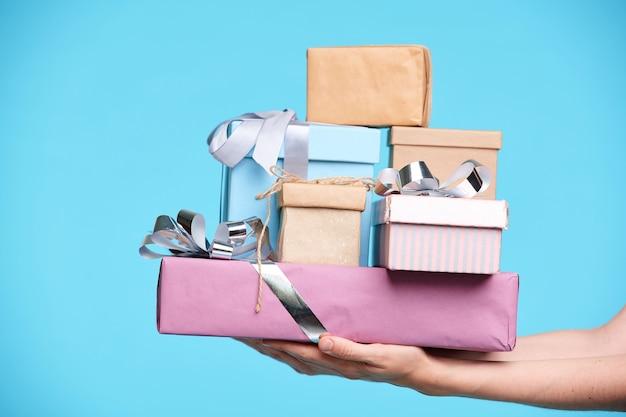 Stapel verpackter und verpackter geschenke in kisten, die von weiblichen händen isoliert an der blauen wand gehalten werden