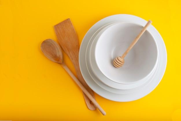 Stapel verschiedene weiße platten, schüsseln. isoliert auf gelbem hintergrund.